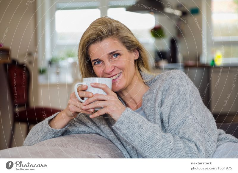 Attractive blonde woman relaxing at home Beverage Coffee Lifestyle Joy Happy Contentment Relaxation Leisure and hobbies Sofa Woman Adults Smiling Friendliness