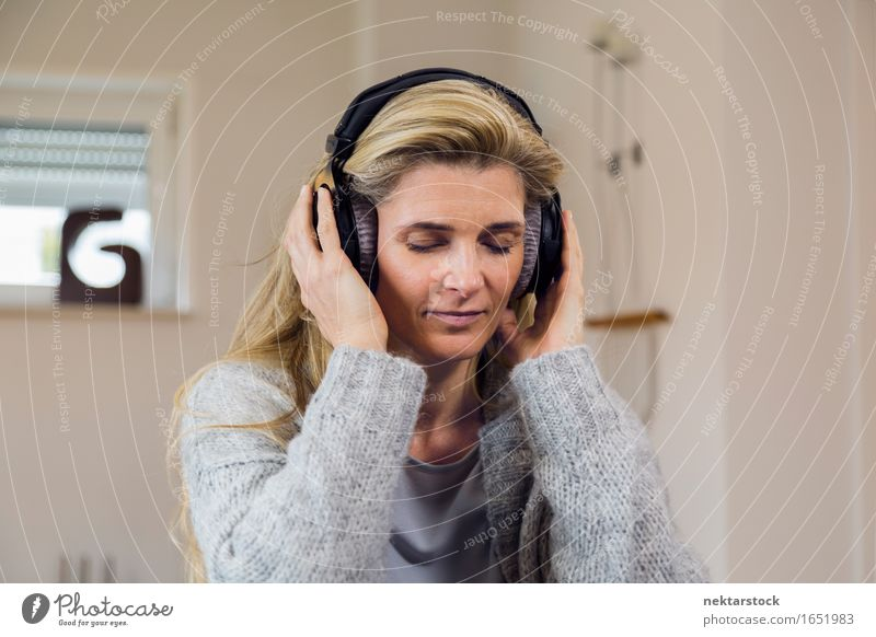 Pretty blonde woman listening to music on couch at home Happy Contentment Relaxation Leisure and hobbies Entertainment Music Woman Adults Blonde Listening
