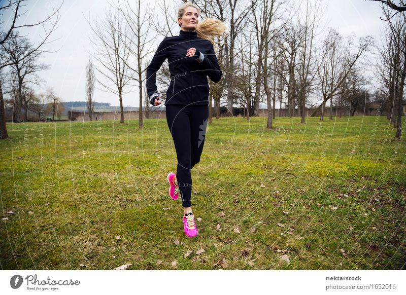 blonde woman running in park Lifestyle Body Wellness Winter Sports Jogging Human being Woman Adults Grass Park Movement Fitness Athletic Speed Practice healthy