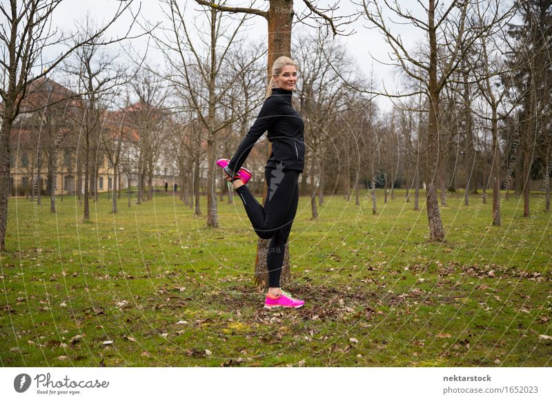 woman stretching right leg in park Lifestyle Body Wellness Calm Winter Sports Human being Woman Adults Tree Park Fitness Smiling Stand Athletic Thin