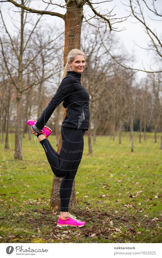 woman stretching her legs in park Lifestyle Body Wellness Sports Human being Woman Adults Park Fitness Smiling Stand Athletic Thin Friendliness limbering up