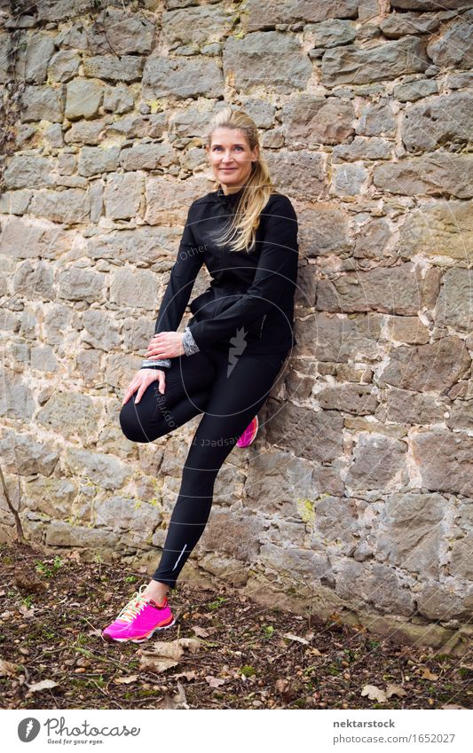 portrait of woman leaning against a wall in park Lifestyle Happy Body Wellness Sports Human being Woman Adults Park Stone Fitness Smiling Athletic Thin