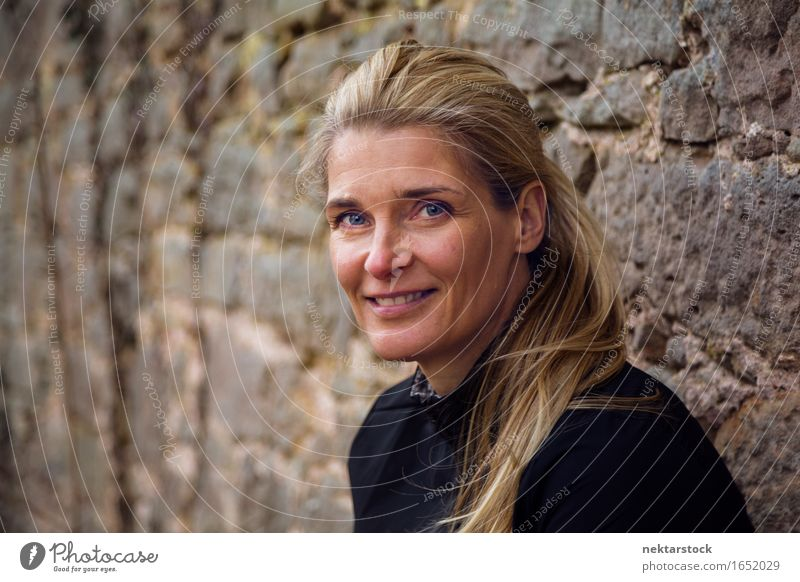 portrait of woman leaning against a wall in park Lifestyle Happy Contentment Calm Human being Woman Adults Blonde Stone Smiling Friendliness Natural