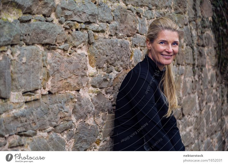 portrait of woman leaning against wall in park Lifestyle Happy Contentment Calm Human being Woman Adults Blonde Stone Smiling Friendliness Natural