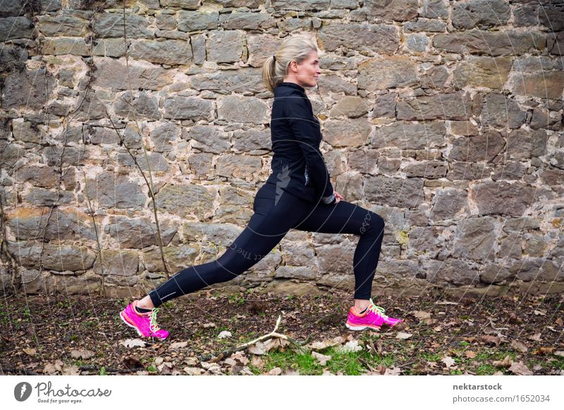 Woman stretching her body in front of ancient wall in park Lifestyle Body Wellness Sports Human being Adults Park Stone Touch Fitness Athletic Mobility Practice