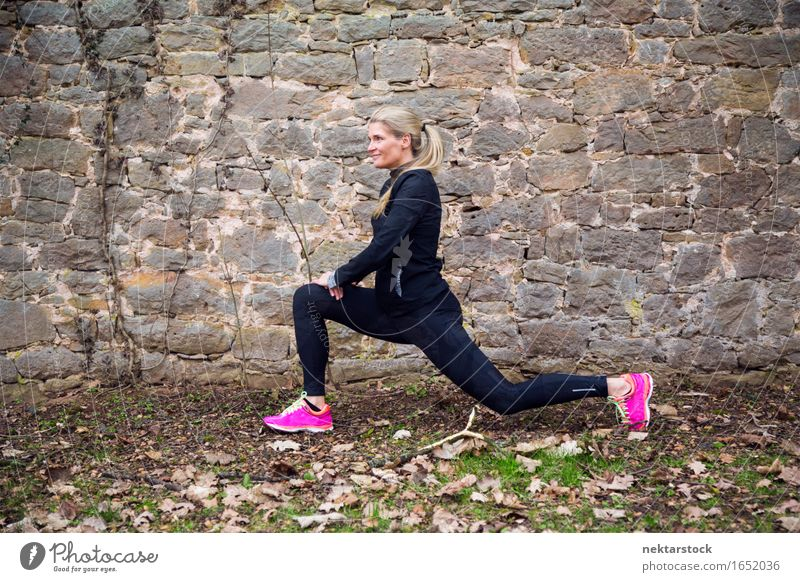 Woman stretching her body in front of ancient wall in park Lifestyle Happy Body Wellness Sports Human being Adults Park Stone Fitness Smiling Athletic