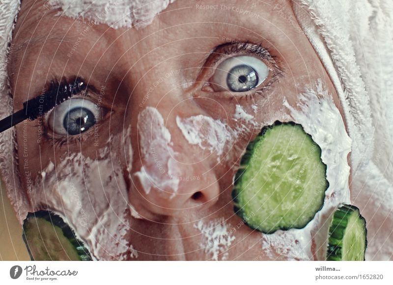Woman with quark mask and cucumber slices on her face is putting on make-up Beautiful Skin Face Cosmetics Cream Make-up Mascara Slices of cucumber Feminine