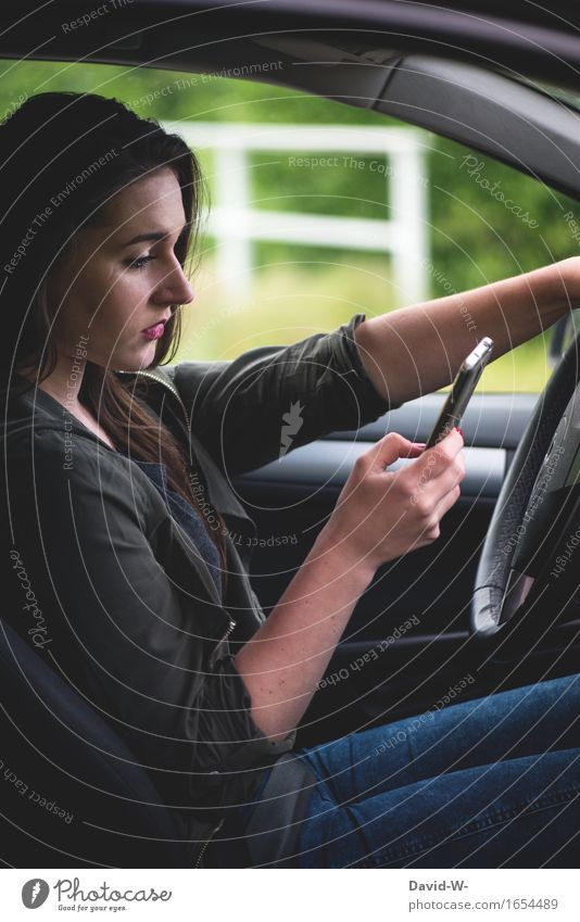 Mobile phone at the wheel Woman youthful car Motoring peril distracted perilous SMS whatsapp news underestimated Typing Looking away Risk hands Steering wheel