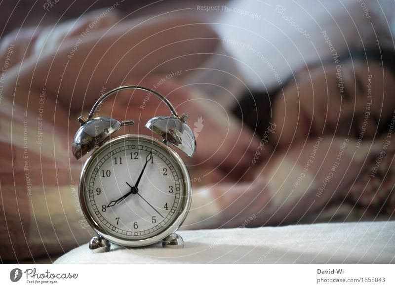 sleeping young woman with alarm clock in the foreground which indicates after 8 o'clock Woman Young woman asleep Oversleep Sleep Alarm clock late riser Time