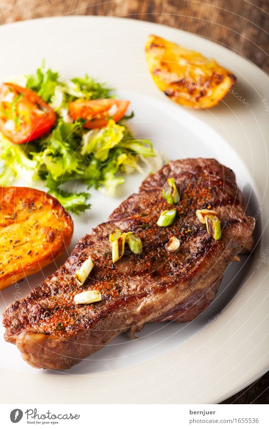 Grilled steak with roasted potatoes Meat Lunch Dinner Plate Restaurant Media Dark Delicious Juicy beef steak Steak Beef grilled Roasted Potatoes Tomato Lettuce