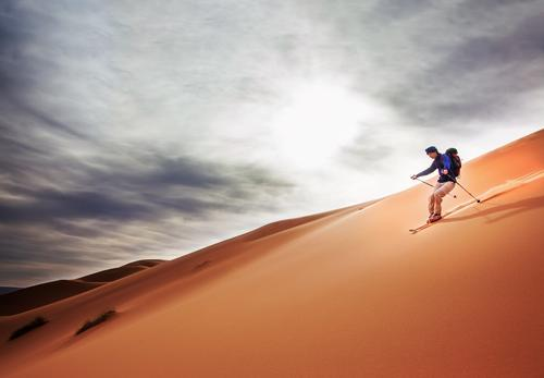 A skier goes downhill on a big sand dune in Sahara desert. Human being Vacation & Travel Man Landscape Adults Yellow Sports Freedom Sand Hiking Trip