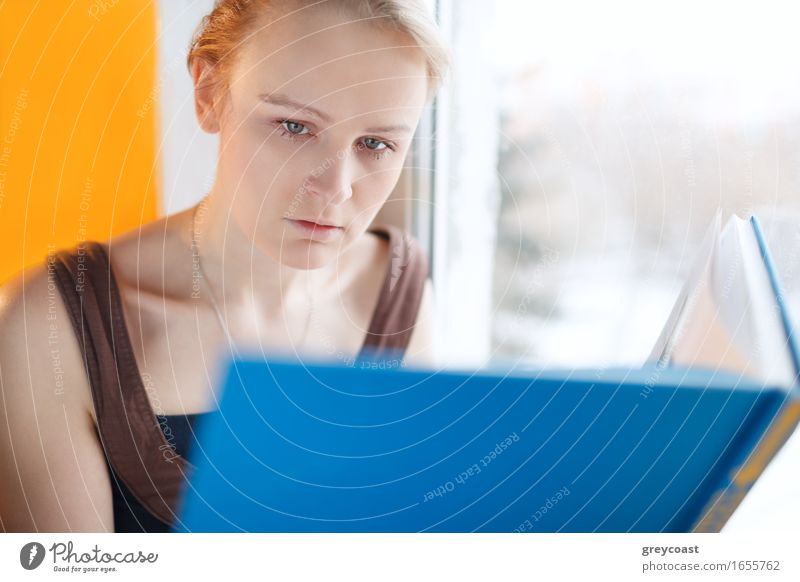 Young woman reading a book with blue cover Human being Youth (Young adults) Blue Beautiful White Relaxation Loneliness House (Residential Structure) Girl