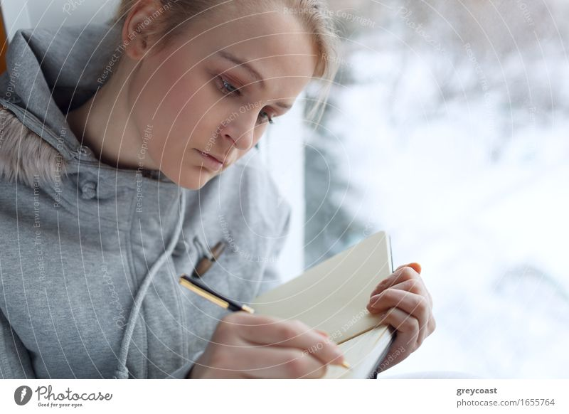 Young girl writing in her journal. Human being Woman Youth (Young adults) Young woman Calm Girl Winter Adults Natural Think Gray Dream Office Body Sit Book