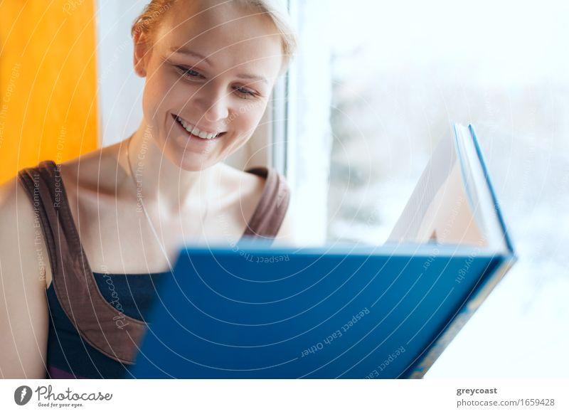 Young smiling woman reading a book Human being Woman Youth (Young adults) Blue Beautiful Young woman White Relaxation Loneliness House (Residential Structure)