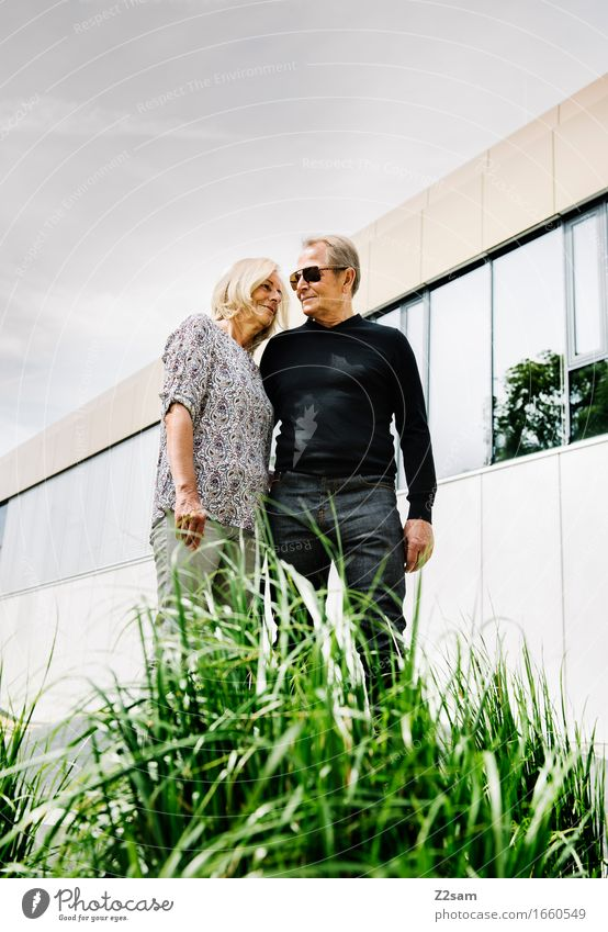 forever Female senior Woman Male senior Man Couple Partner 60 years and older Senior citizen Summer Beautiful weather Bushes Downtown Jeans Smiling Love Stand
