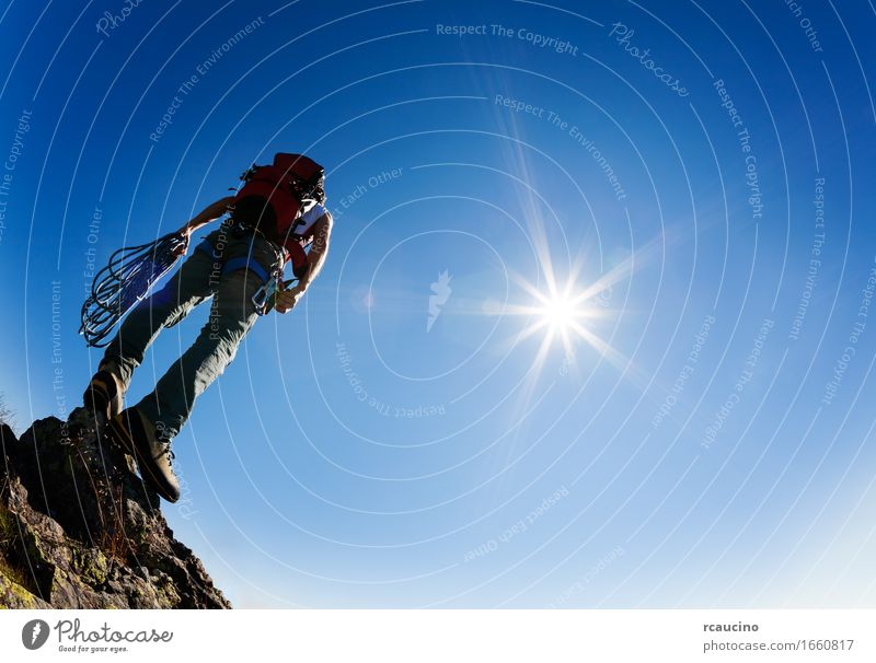 Climber stands on a rock at the end of his rout Human being Sky Nature Man Blue Sun Landscape Loneliness Mountain Adults Sports Stone Rock Hiking Success Stand