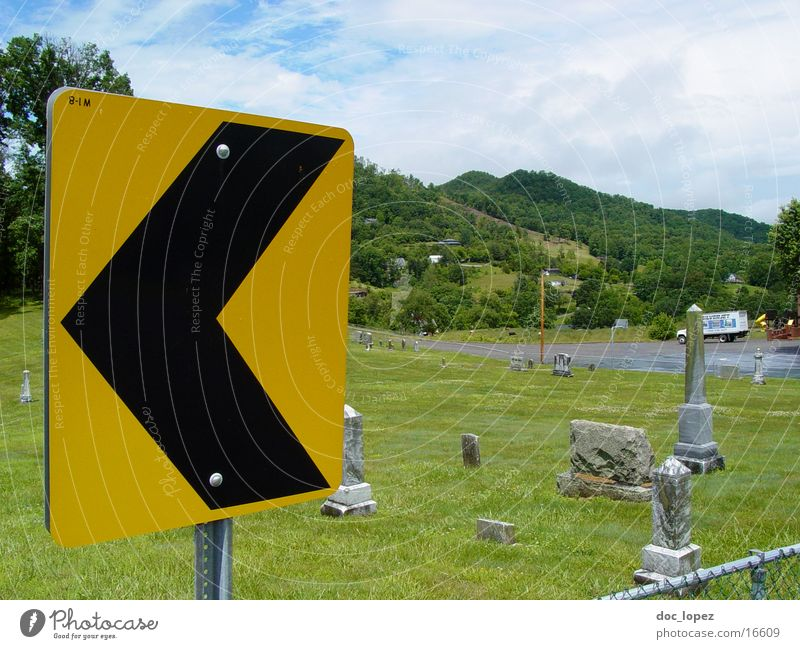 left Curve Yellow Black Warning label Green Cemetery Meadow Grave Signs and labeling Landscape USA traffic sign pointing left that predicts a curve...