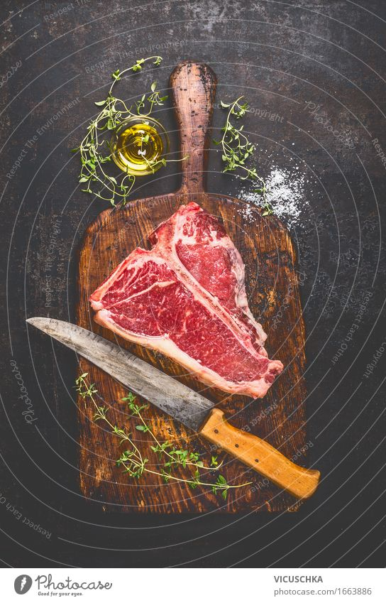T-Bone Steak on old cutting board with knife Food Meat Herbs and spices Cooking oil Nutrition Lunch Dinner Picnic Organic produce Knives Style Healthy Eating