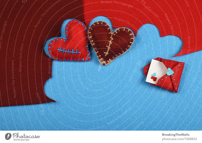 Two stitched toy hearts, brown and red cut out on blue felt Leisure and hobbies Handcrafts Art Work of art Piece of paper Toys Heart Communicate Love Near Blue