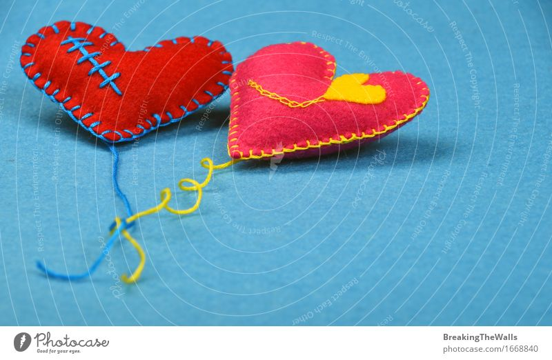 Two toy hearts with threads, red and pink on blue felt Blue Red Yellow Love Art Together Pink Leisure and hobbies Creativity Heart Gift Romance Soft Wedding Near Toys