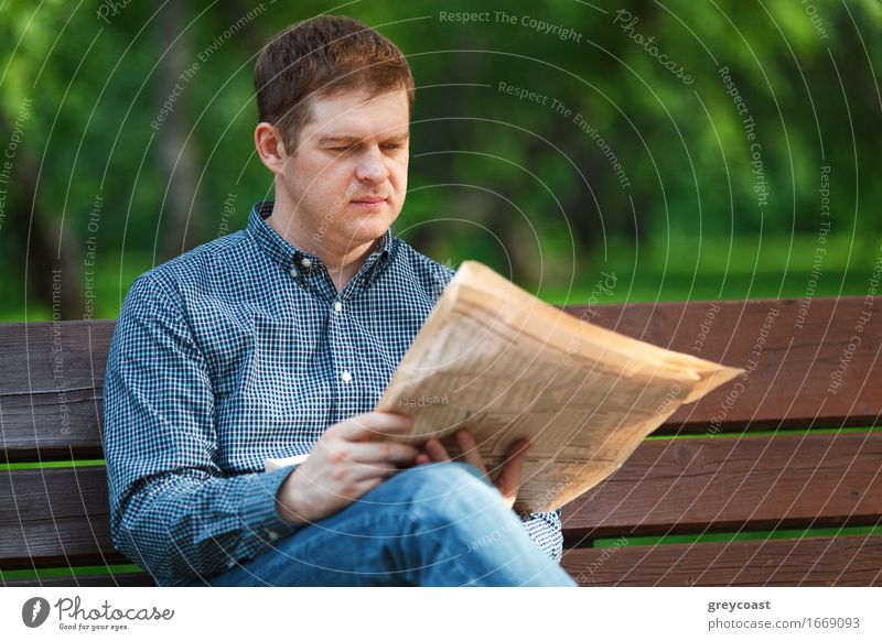 Man reads newspaper on bench in the park Lifestyle Happy Relaxation Reading Garden Business Human being Young man Youth (Young adults) Adults 1 18 - 30 years