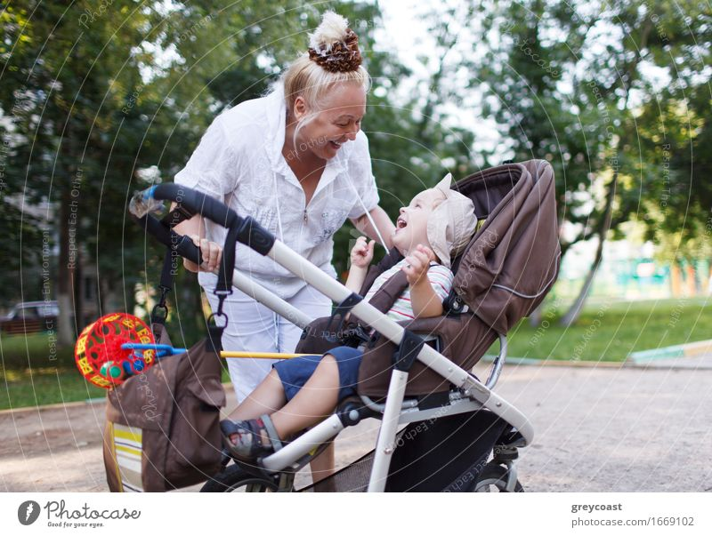 Granny playing with her grandson in a baby stroller in the yard. Lifestyle Joy Happy Beautiful Playing Garden Child Human being Baby Boy (child) Woman Adults