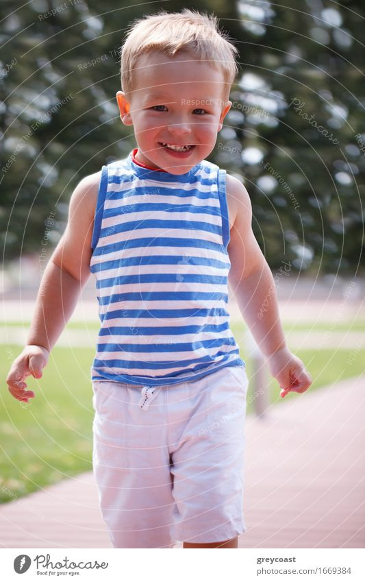 Portrait of smiling happy 3 year old boy in striped vest running in the city park and looking to the photographer Lifestyle Joy Happy Beautiful Face