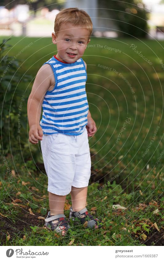 Portrait of 3 year old boy in striped vest in the city park looking to the photographer and smiling Lifestyle Joy Happy Beautiful Face Leisure and hobbies