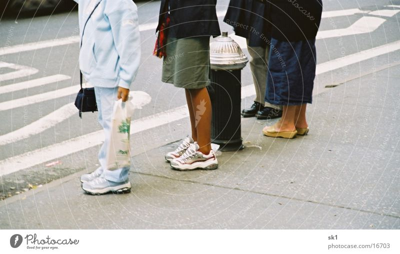 legs Footwear Dark Fire hydrant Bus stop Sidewalk Group Legs Bright Human being Street Wait Queue