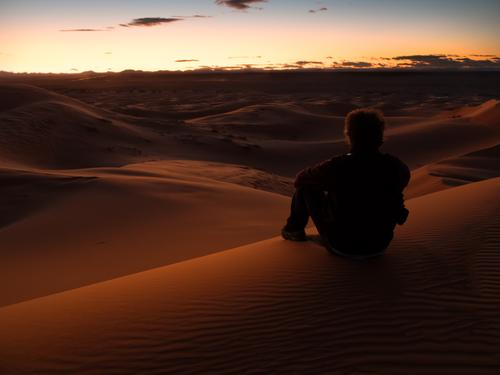 Man sitting on a dune in the desert while watching the sunset Human being Nature Vacation & Travel Summer Beautiful Colour Landscape Relaxation Red Loneliness