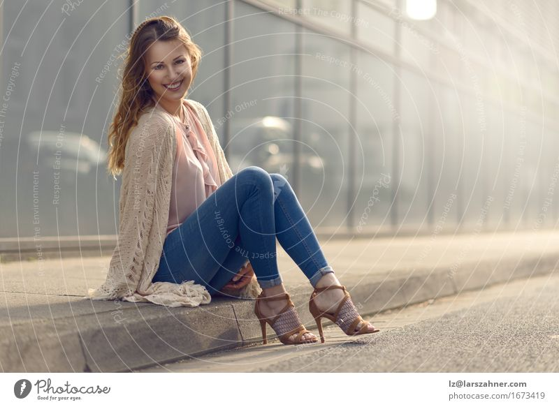 Smiling young woman relaxing on sidewalk Beautiful Face Feminine Woman Adults 1 Human being 18 - 30 years Youth (Young adults) Street Fashion High heels