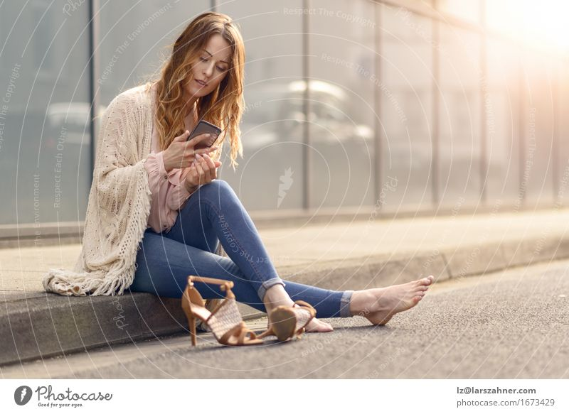 Attractive young woman reading on her mobile phone Woman Beautiful Relaxation Face Adults Street To talk Lifestyle Copy Space Hair Sit Reading Telephone Hip & trendy Long Fatigue