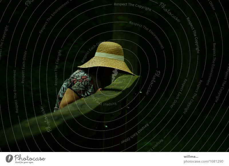 woman with straw hat bends over the railing of a wooden bridge against a dark background Feminine Woman Adults Hat Straw hat Dark Curiosity Black Hope Sadness