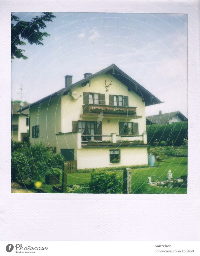 A typical Bavarian detached house with balconies and deer antlers. Houses in the background and garden in the foreground. Settlement in a rural area. Neighbourhood