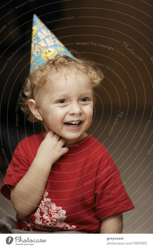 Cute happy young boy in a party hat laughing with enjoyment as he celebrates a birthday or Christmas Lifestyle Joy Happy Beautiful Face Decoration