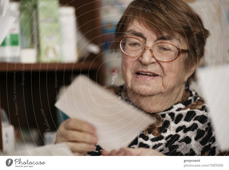 Elderly woman wearing glasses sitting in her living room reading a letter, closeup portrait Lifestyle Face Reading Teacher Retirement Human being Woman Adults