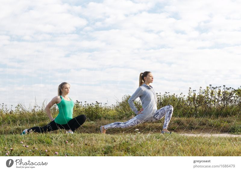 Two attractive athletic young girls exercising outdoors in the countryside doing stretching exercises to stay fit and tone their muscles Lifestyle Joy Beautiful