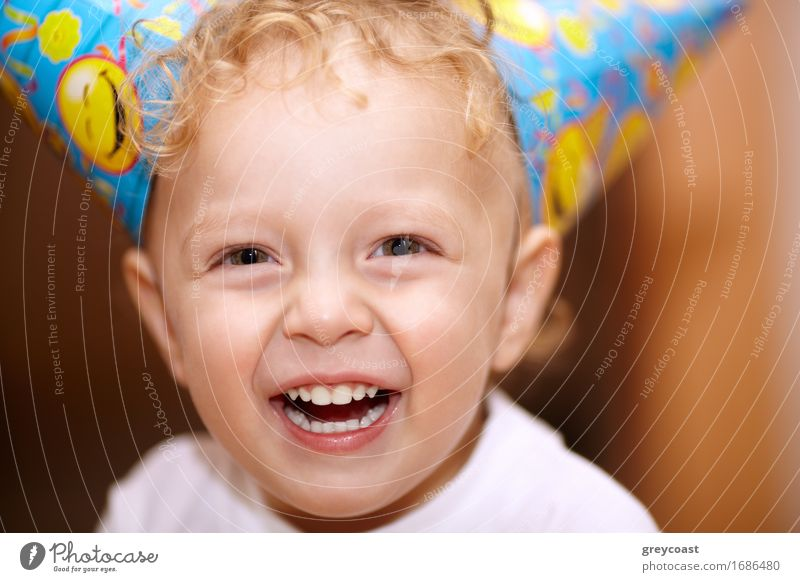 Closeup facial portrait of a happy laughing little boy with wavy blond hair looking directly into the camera Joy Happy Summer Feasts & Celebrations Birthday