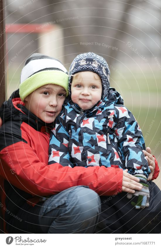 Two adorable young brothers outdoors in winter wrapped up warmly against the chill weather with the older boy cuddling his toddler sibling on his lap Joy Garden