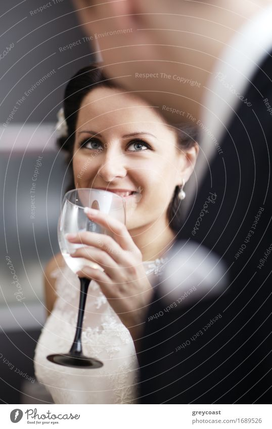 Elegant young woman in a white dress drinking white wine at a function and smiling up at her male partner Alcoholic drinks Champagne Happy Beautiful