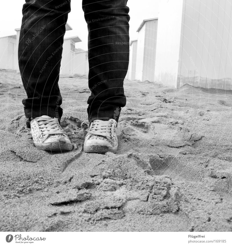 Human being Vacation & Travel Ocean Loneliness Beach Wall (building) Wall (barrier) Sand Think Legs Feet Footwear Empty Stand Jeans Sneakers
