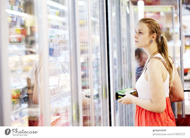 Young woman buying dairy or refrigerated groceries at the supermarket in the refrigerated section opening glass door of the fridge Lifestyle Shopping