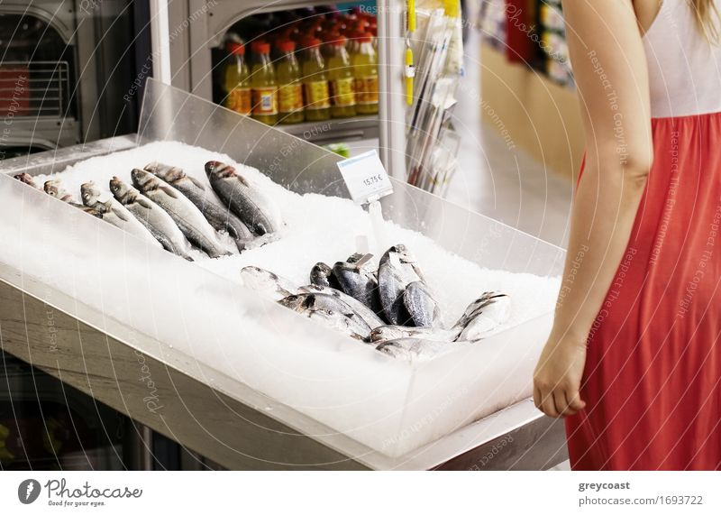 Woman shopping for fish in a supermarket standing looking at a display of fresh whole fish on ice Fish Lifestyle Shopping Happy Human being Young woman