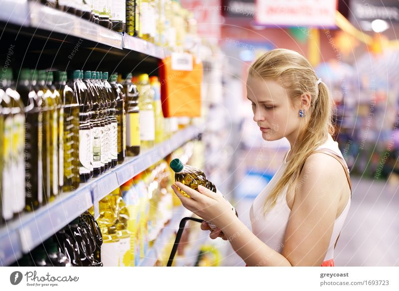 Young blond woman picking an olive oil bottle from the shelves of a supermarket and reading the label Bottle Shopping Young woman Youth (Young adults) Woman