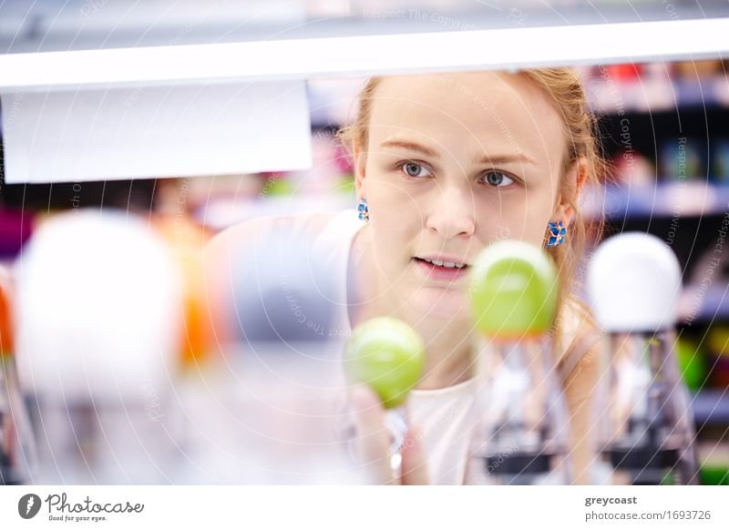 Young blond woman carefully analyzing products in a store - view through products Shopping Young woman Youth (Young adults) Woman Adults 1 Human being