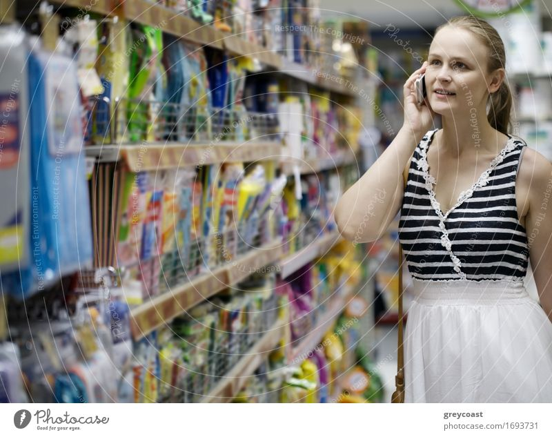 Woman with a long blond ponytail chatting on her mobile while out shopping standing in an aisle in the supermarket Shopping Happy Telephone Cellphone PDA