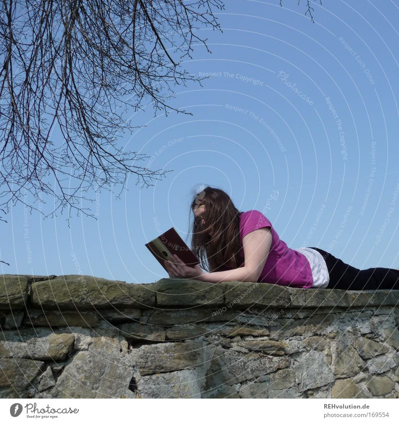 woman reading on a wall Colour photo Copy Space top Day Contentment Relaxation Calm Leisure and hobbies Reading Feminine Young woman Youth (Young adults) 1