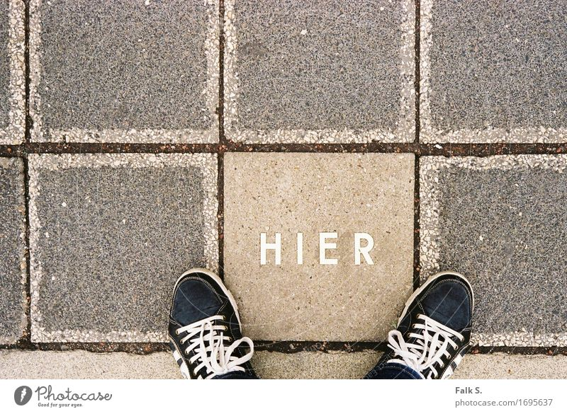 H I E R Feet Concrete slab Pedestrian Footpath Footwear Stone Characters Capital letter Language Stand Wait Sharp-edged Firm Under Warmth Gray Unwavering