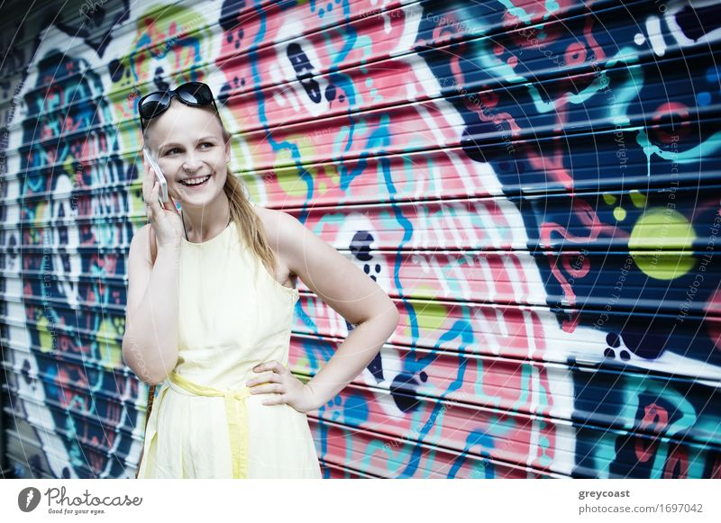 Smiling woman in yellow dress standing and chatting on her smart phone in front of graffiti painted on corrugated iron Lifestyle Style Happy Beautiful Summer