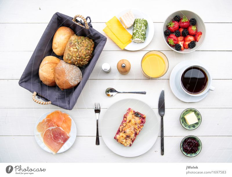 delicate breakfast at a white table with different ingredients Food Sausage Fish Cheese Yoghurt Dairy Products Fruit Dough Baked goods Roll Cake Jam Breakfast